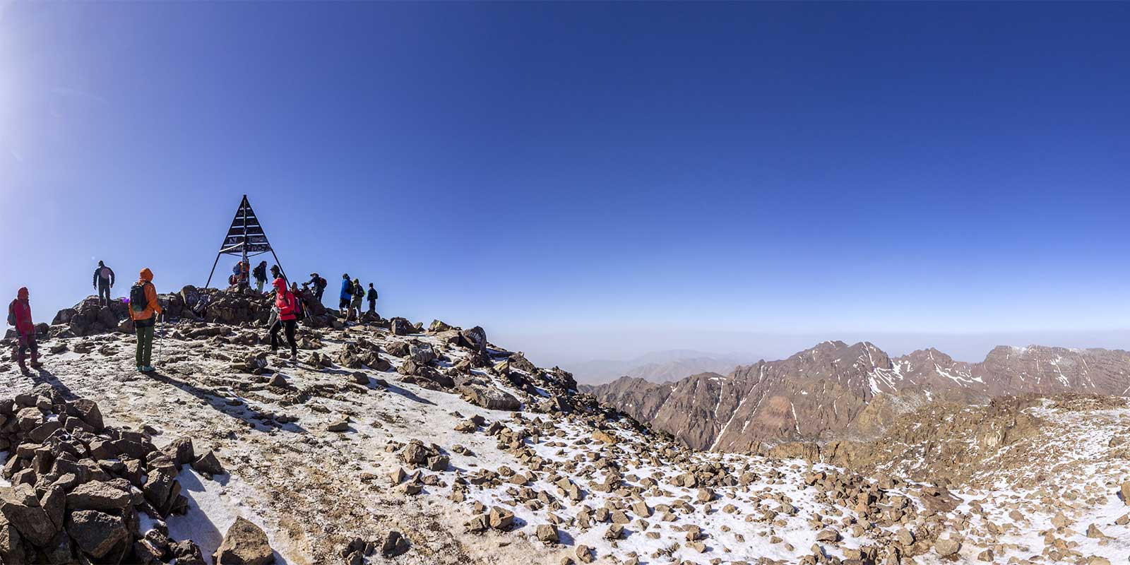 Trekkers at Mount Toubkal snow-covered summit with mountain scenery