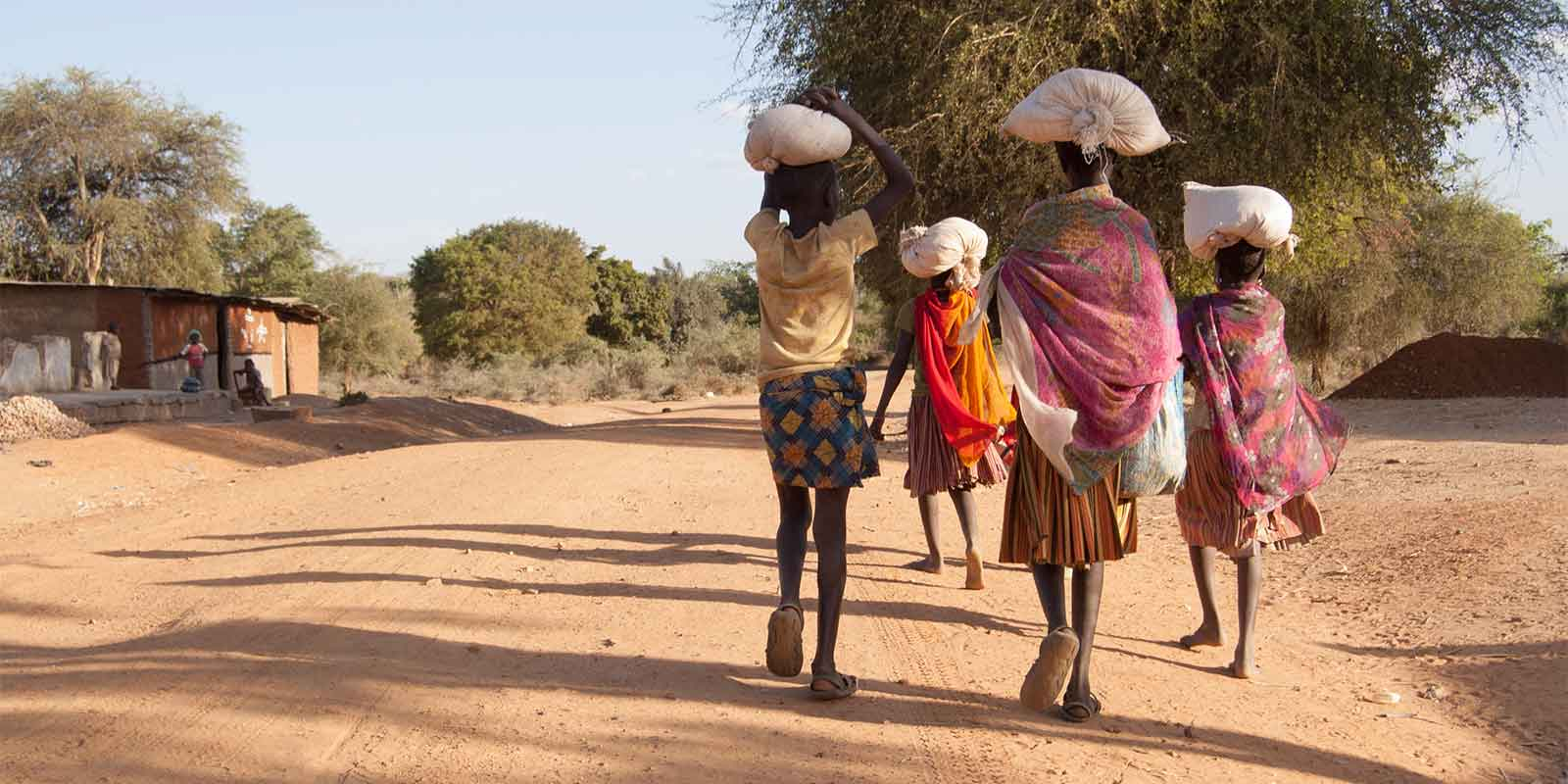 African women carrying supplies to their village community