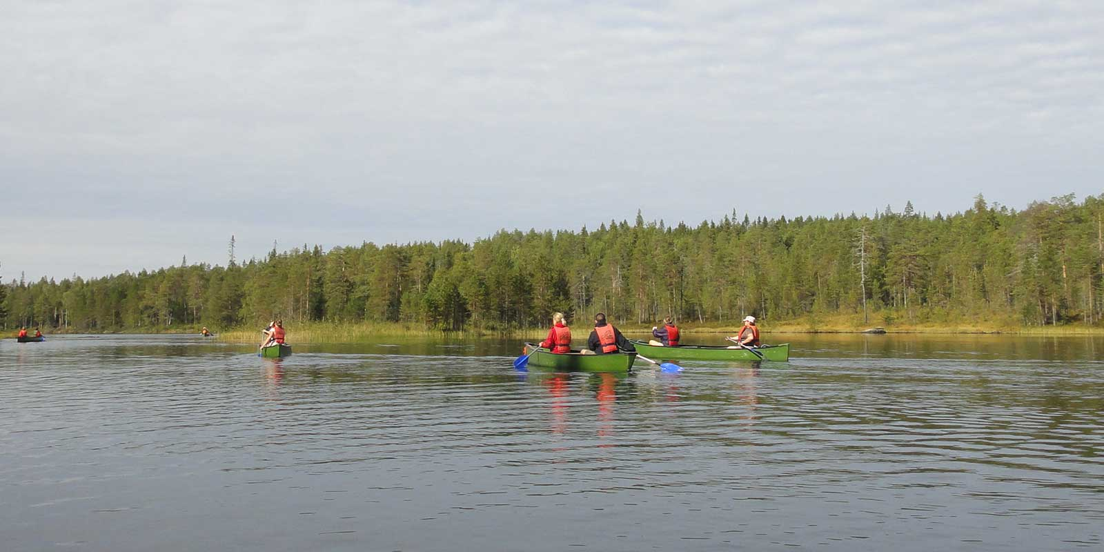 Group canoeing on river in Finland