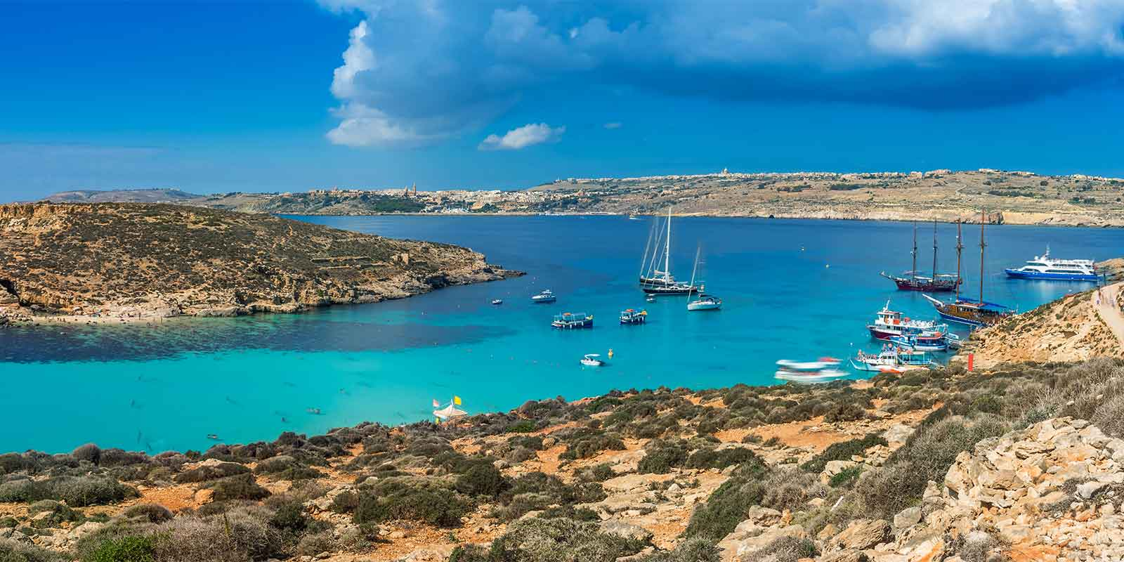 Panorama of turquoise Blue Lagoon and boats on Comino Island, Malta