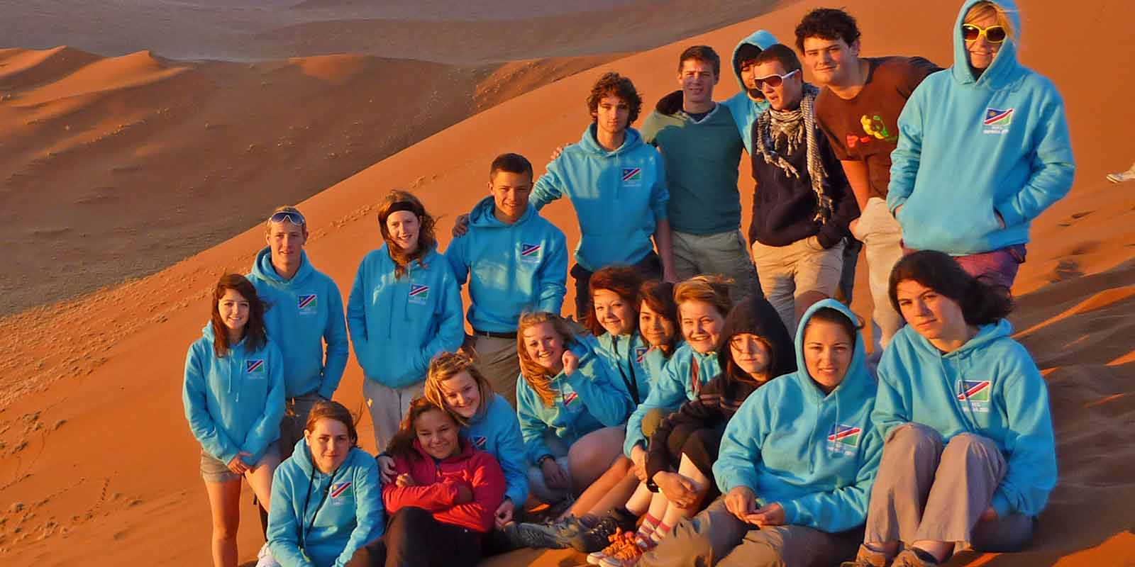 A group of students gathered at the top of a desert dune in the evening sun