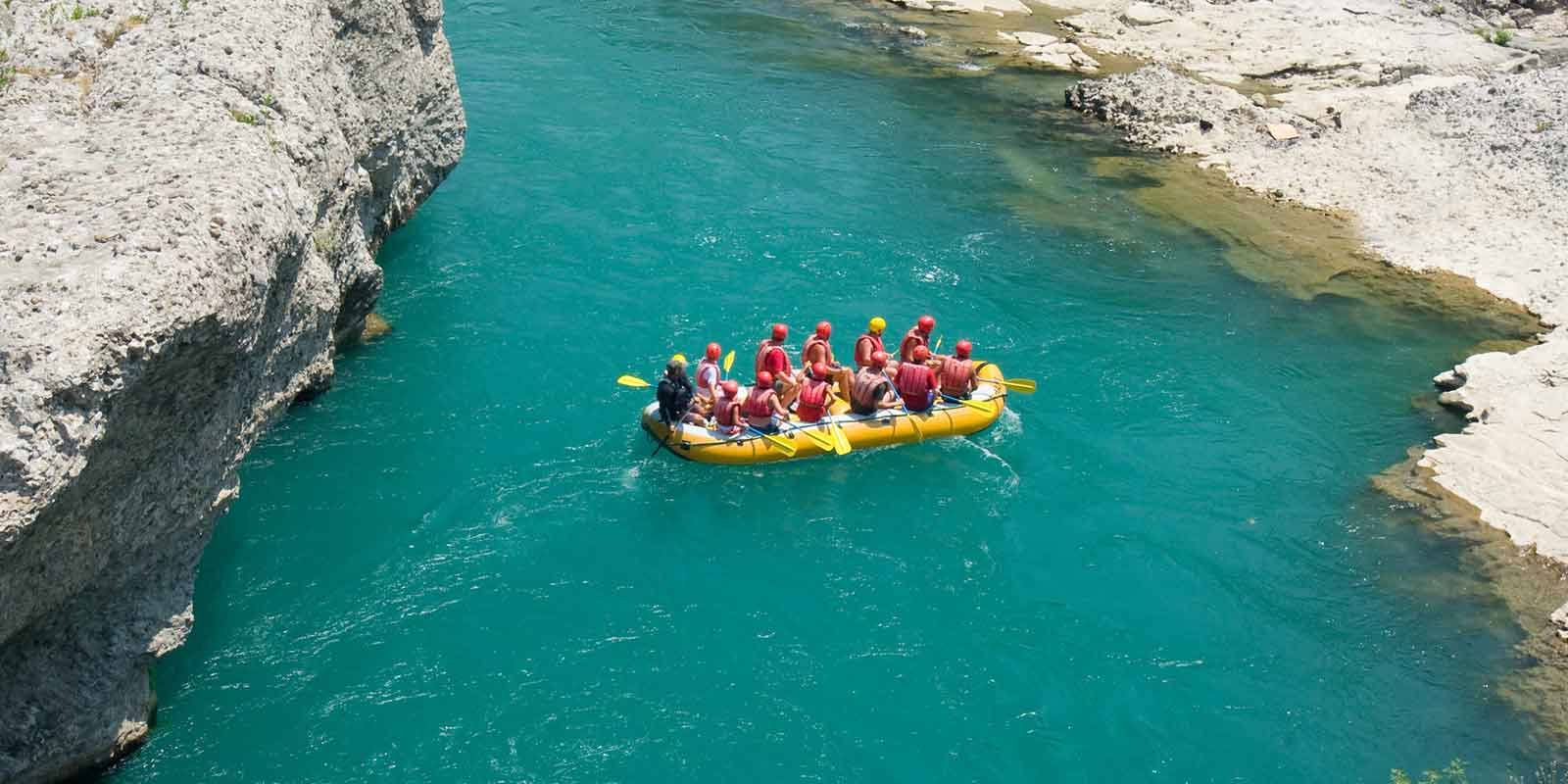 Aerial view of group rafting in a turquoise river with rocky cliffs either side