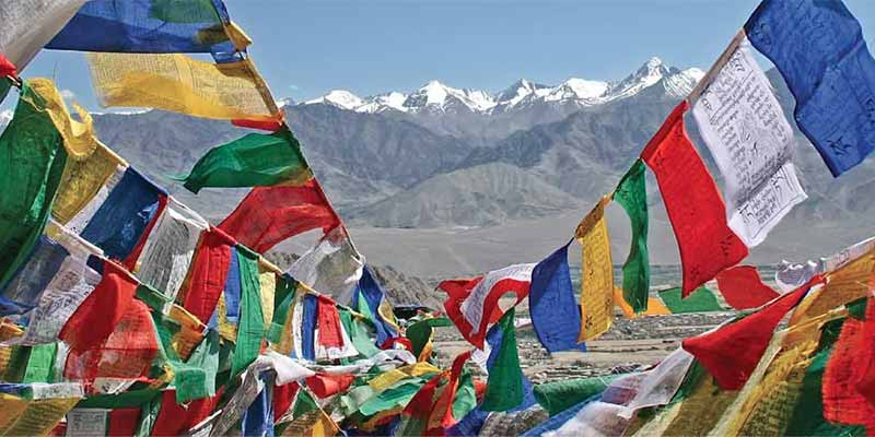 Prayer flags flying against a backdrop of the snow-capped Himalayas