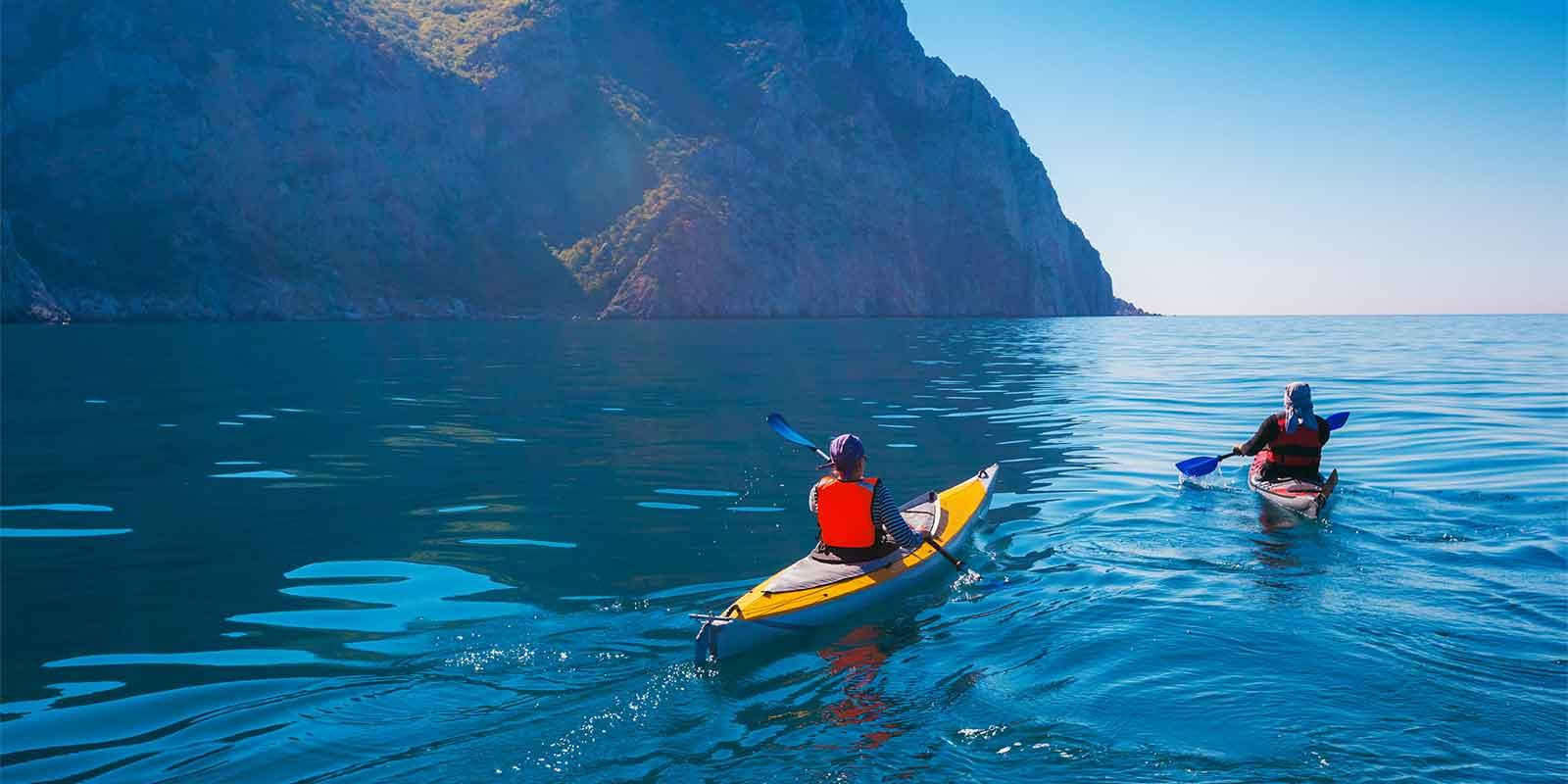 Pair of kayakers paddling around the coast