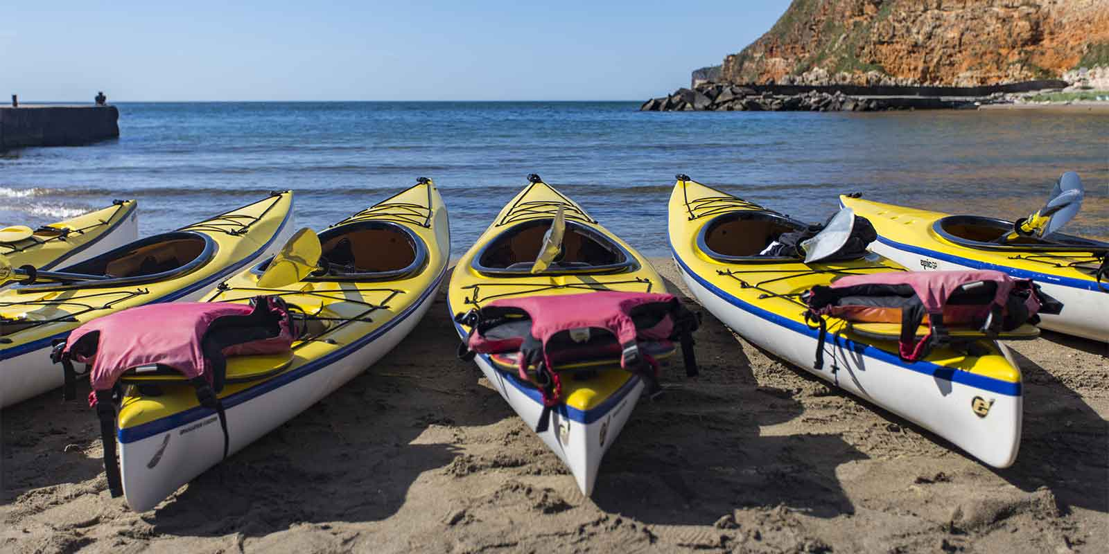 Kayaks and lifejackets waiting on the beach