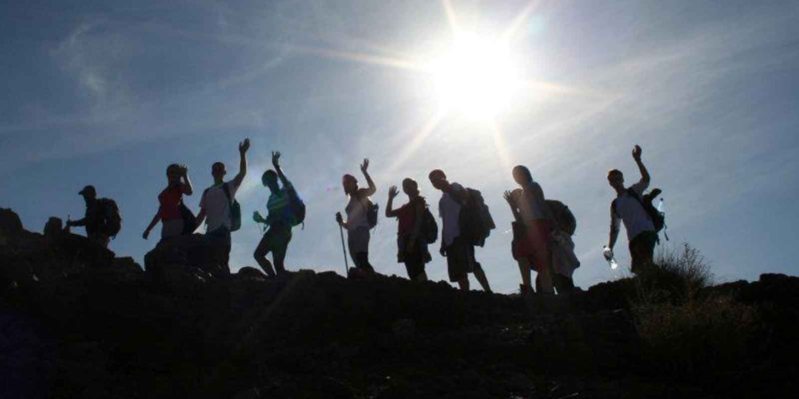 School group trekking with bright sun in background