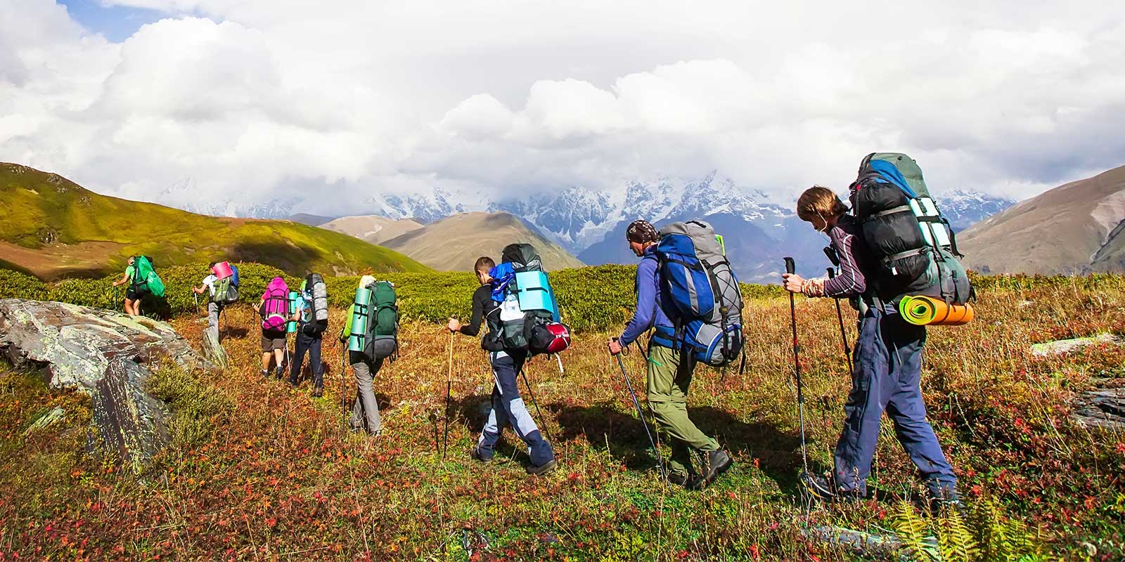 Group trekking with camping gear in mountains