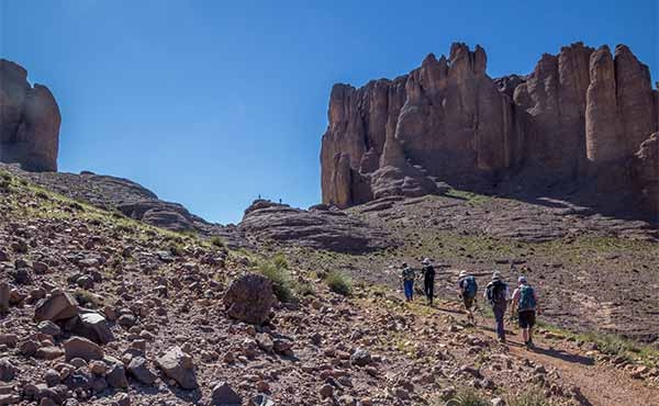 Group trekking in Jebel Sahro mountain range surrounded by rocky peaks
