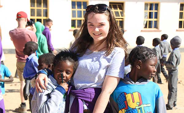 British school girl with local children in Namibia school on school group visit
