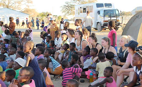 British school group with school children in village in Namibia