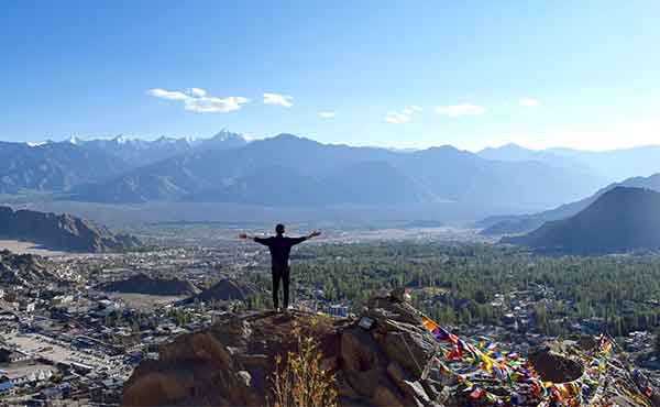 Trekker standing on summit overlooking Leh surrounded by Himalayas