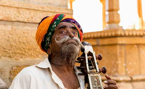 Sadhu holyman playing an instrument outside temple in India