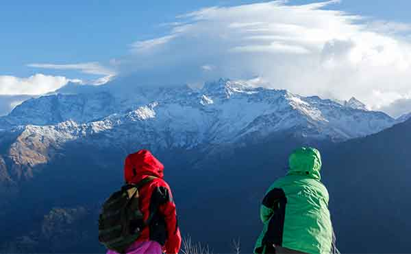 Two trekkers on summit of Poon Hill looking out to Annapurna range