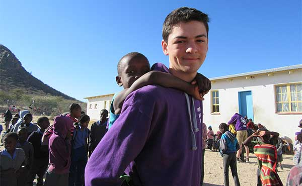Student with young pupil on his shoulders at a school in Namibia