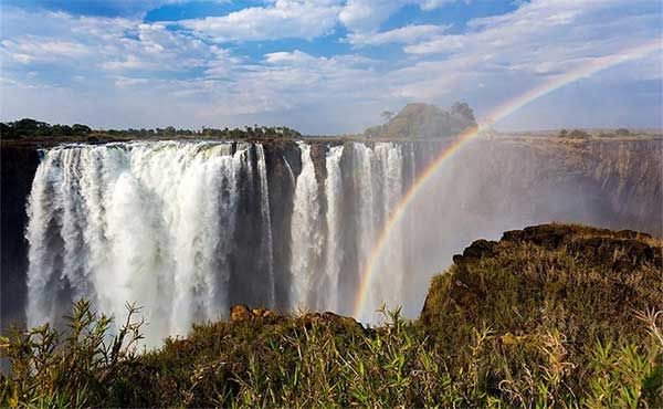 A rainbow in the foreground with Victoria Falls in the background