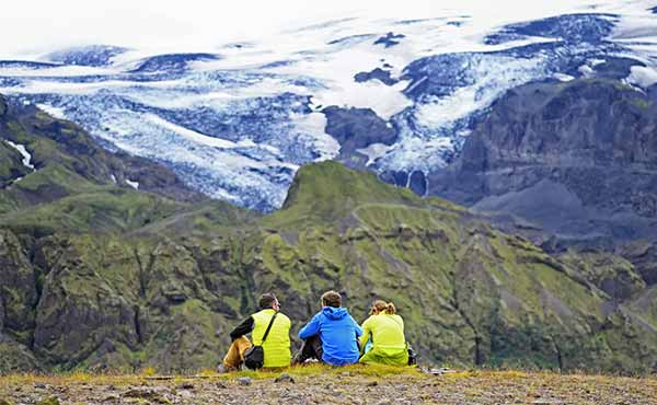 Three hikers sitting overlooking a valley in Thorsmork, Iceland