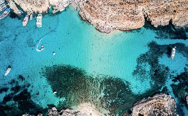 Aerial image taken by a drone of Blue Lagoon and boats on Comino Island Malta