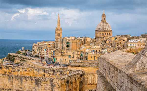 View of buildings in Malta's capital city of Valetta, with the Mediterranean sea in the background