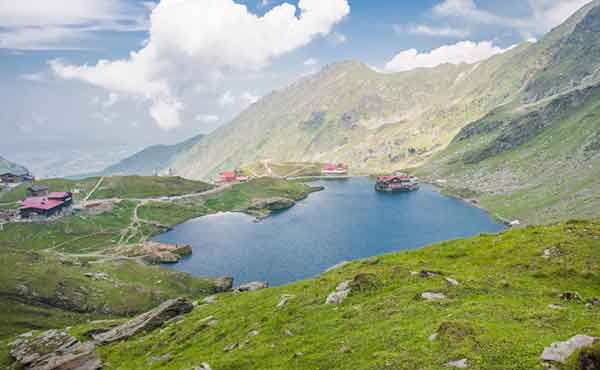 Balea Lake and cottages surrounded by Fagaras mountains