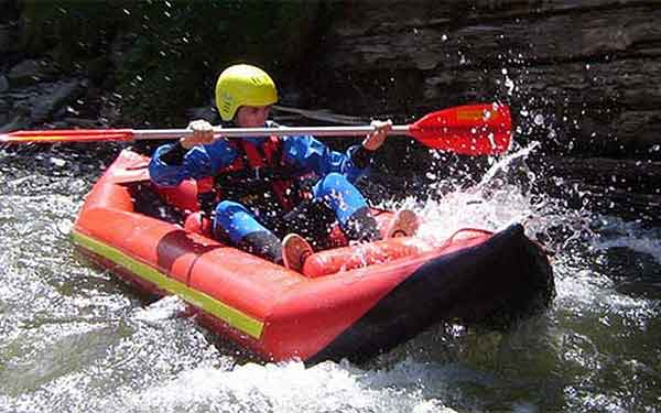 Student traversing white-water in an inflatable kayak